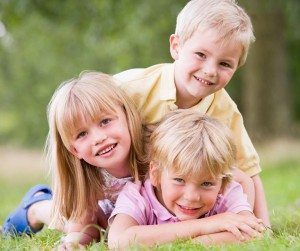 B3FB0K Three young children playing outdoors smiling