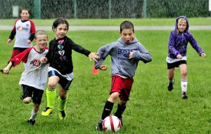 Staff photo by David Leaming SCORE: The pouring rain did not stop these kids including Luke Carey as he breaks free with ball during practice in the Challenger Sports soccer program at Carrabec High School on Tuesday.